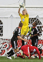 Troy Perkins #23 of D.C. United pulls in the ball over Wilman Conde #22 of the Chicago Fire during an MLS match on April 17 2010, at RFK Stadium in Washington D.C.