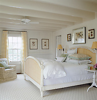 Framed seashell prints hang on the walls of this white traditional double bedroom.