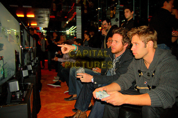 AJ BUCKLEY & SHAUN SIPOS.At the Launch of Battlefield Bad Company 2 presented by Electronic Arts and GameStop held at MI6, West Hollywood, CA, USA, .18th February 2010 .half length sitting playing computer game finger pointing profile side .CAP/ADM/BSR.©Ben Schneider/Ratianda/AdMedia/Capital Pictures.