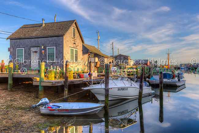 The commercial fishing village of Menemsha and boats docked in Menemsha Basin lit by golden light during the first hour after sunrise, in Chilmark, Massachusetts on Martha's Vineyard.