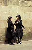 Spain. Andalusia/Andalucia.  Two elderly widows stop for a chat by the town's old walls..
