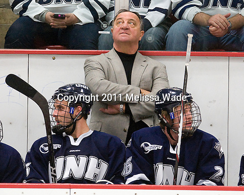 John Henrion (UNH - 16), Dick Umile (UNH - Head Coach), Greg Burke (UNH - 26) - The Harvard University Crimson defeated the University of New Hampshire Wildcats 7-6 on Tuesday, November 22, 2011, at Bright Hockey Center in Cambridge, Massachusetts.