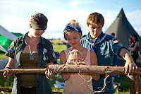 Two Swedish scouts are teaching a younger friend how to tie correctly while building camp. Photo: Kim Rask/Scouterna
