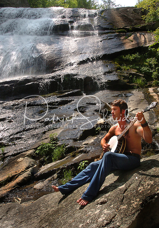 A visitor to the Harper Creek Waterfall in the North Carolina mountains plays a banjo while sitting on the rocks by the falls.