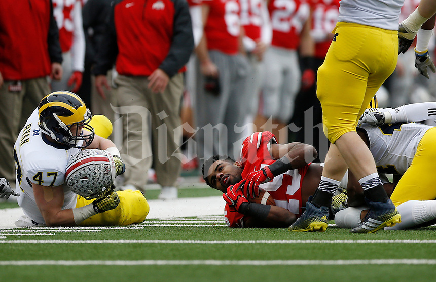 Michigan Wolverines linebacker Jake Ryan (47) ends up holding the helmet of Ohio State Buckeyes running back Ezekiel Elliott (15) after it was ripped off at the end of a run during the third quarter of the NCAA football game at Ohio Stadium on Nov. 29, 2014. The Buckeyes won 42-28. (Adam Cairns / The Columbus Dispatch)