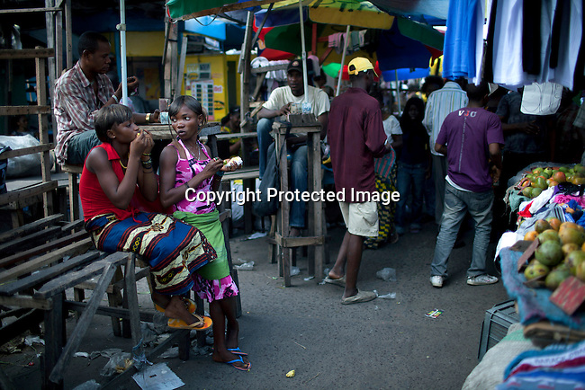 KINSHASA, DRC - OCTOBER 30: Esther Yandakwa, a 13-year old homeless child talks to a friend in the central market of Kinshasa, DRC. She has lived on the streets since she was 6-7 years old and is dependent on prostitution to survive. She is walking the streets of Kinshasa to look for customers. She uses drugs and lives with a group of other homeless people in central Kinshasa. Thousands of children live on the streets of Kinshasa. Esther has been in and out orphanages or but she is only happy living in the mean streets of Kinshasa. (Photo by: Per-Anders Pettersson)