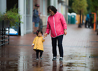 NWA Democrat-Gazette/CHARLIE KAIJO Katherine Park, 1, walks with her grandmother Jung Park of New York (from left) after a brief downpour, Sunday, October 7, 2018 at the downtown square in Bentonville.