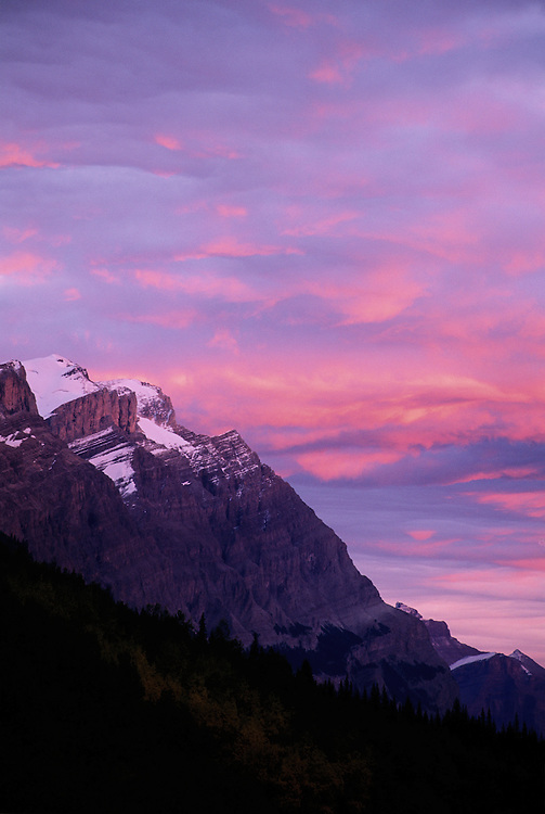Mount Wilson with snow remnants, and soft summer sunset creating painterly clouds, Banff National Park, Alberta.