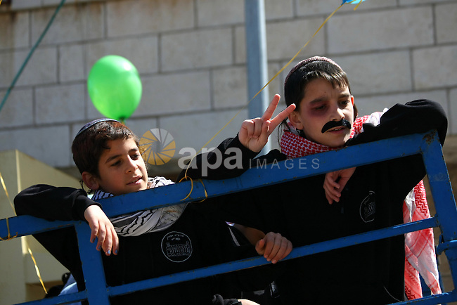 Israeli settlers wear Palestinian Keffiyehs during celebrations marking the Jewish holiday of Purim in the occupied West Bank city of Hebron March 5, 2015. Purim is a celebration of the Jews' salvation from genocide in ancient Persia, as recounted in the Book of Esther. Photo by Mamoun Wazwaz