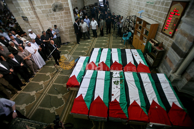 Palestinians pray next to flag-covered coffins containing the remains of Palestinian militants in a mosque in Gaza City May 31, 2012. The remains of 91 Palestinian militants whose attacks killed hundreds of Israelis over the past 35 years were returned to the West Bank and Gaza on Thursday in a gesture Israel said it hoped could help revive peace efforts. Photo by Ali Jadallah