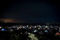 This is a view from the Central Tower, east out over Summer sub camp. You can see the lights from the kitchen tents in different colours all over the field. The tornado looking light at the left is smoke from a far away power plant. Photo: Eric Hampusgård/Scouterna