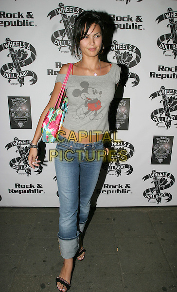 GABRIELLE RICHENS.Christmas in July - fashion show and party.Pangea, 85 Picadilly, London W1.July 13th, 2004.full length, mickey mouse t shirt, denim, jeans, floral print bag.www.capitalpictures.com.sales@capitalpictures.com.© Capital Pictures.