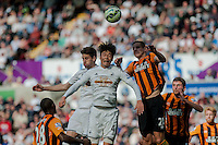 SWANSEA, WALES - APRIL 04: Ki Sung-Yueng of Swansea City  jumps for the ball during the Premier League match between Swansea City and Hull City at Liberty Stadium on April 04, 2015 in Swansea, Wales.  (photo by Athena Pictures)