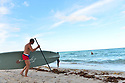 HALLANDALE BEACH, FL - MARCH 17: People Paddleboard on a almost empty beach. Barricades and Signage indicates that an area of Hallandale Beach is closed on March 17, 2020 in Hallandale Beach, Florida. Republican Florida Gov. Ron DeSantis and Hallandale Beach City officials closed the area of the beach that is popular with college spring breakers and asked them to refrain from large gatherings where COVID-19 could spread on March 17, 2020 in Hallandale Beach, Florida.  ( Photo by Johnny Louis / jlnphotography.com )