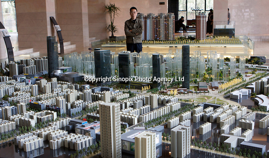 """Potential properties buyers look at the mock up models of """"24 City"""" developed by CR Properties, in its slaes reception hall in Chengdu, China..21 Mar 2008"""