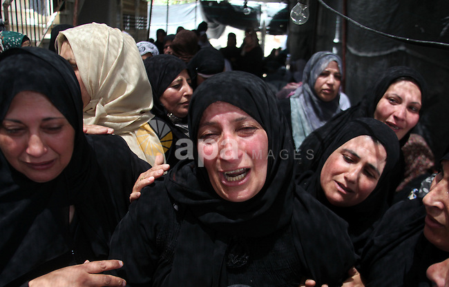 Relatives of Palestinian teenager Mohammed Dudin, mourn during his funeral in the West Bank city of Hebron June 20, 2014. Israeli troops killed a Palestinian teenager in the occupied West Bank on Friday and arrested 25 people, pursuing a weeklong crackdown against Islamist militants and house-to-house searches for three Israeli teenagers who went missing eight days ago. Palestinian medics said Mohammed Dudin, 15, was killed in the village of Dura, near the city of Hebron in the West Bank. The Israeli military said troops had fired live ammunition when rocks and firebombs were thrown at them during an arrest raid. Photo by Mamoun Wazwaz