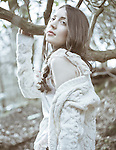 Young woman with long brunette hair wearing white cardigan standing outdoors in woods