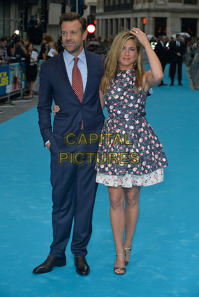 Jason Sudeikis, Jennifer Aniston<br /> 'We're the Millers' European UK film premiere, Empire cinema, Leicester Square, London, England.<br /> 14th August 2013<br /> full length blue pink white sleeveless floral print dress suit red tie arm around waist hand arm in air on head<br /> CAP/PL<br /> &copy;Phil Loftus/Capital Pictures