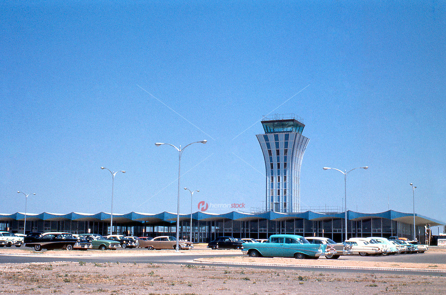 Vintage view of the Robert Mueller Municipal Airport Control Tower and vintage automobiles in the parking lot, Austin, Texas in May, 1961 - Stock Image.