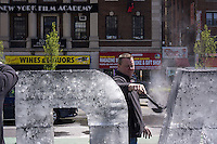 A worker add soot to an ice sculpture by the Dark Snow Project at an Earth Day fair in Union Square Park in New York on Sunday, April 21, 2013.  The Dark Snow Project contends that the ice melt of the glaciers in Greenland is caused by black carbon soot from wild fires and industrial pollution covering the ice and warming it up. If the melting of the ice sheet cannot be slowed sea levels could conceivably rise over six feet by the end of the century exacerbating coastal flooding   (© Richard B. Levine)