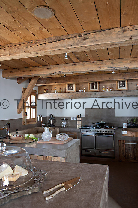 This open plan kitchen successfully combines modern concrete work surfaces and stainless steel splashbacks with the original wooden structure of this 19th century chalet