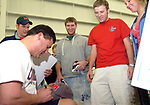 Pat Barham, a senior from Jackson, Andrew Aycock, a freshman from Dallas, Texas, and Angie Swenson, a sophomore from Huntsville, Ala. wait to get an autograph from Ole Miss head coach Ed Orgeron Wednesday evening at the Indoor Practice Facility.  Wednesday evening's practice was open to the students, who turned out by the hundreds. Photo by Nathan Latil/Ole Miss Communications