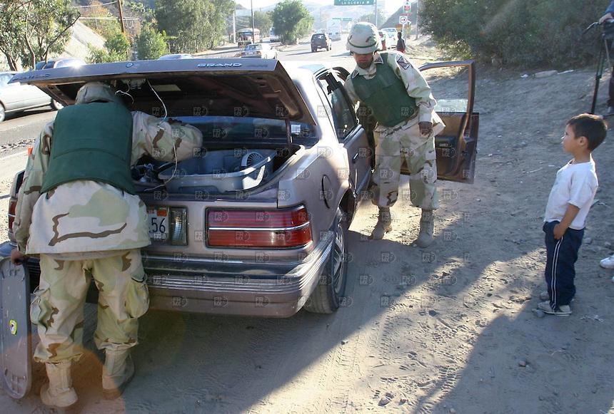 Policias de la PFP y miembros del ejercito trabajan  en la la carretera libre a Rosarito  operado por la PFP y el ejercito en Tijuana en  Baja California Norte durante el operativo que lleva acabo el ejercito, la policia estatal y la Policia Federal Preventiva en la ciudad, el 05 de enero de 2007. Foto: Alejandro Meléndez