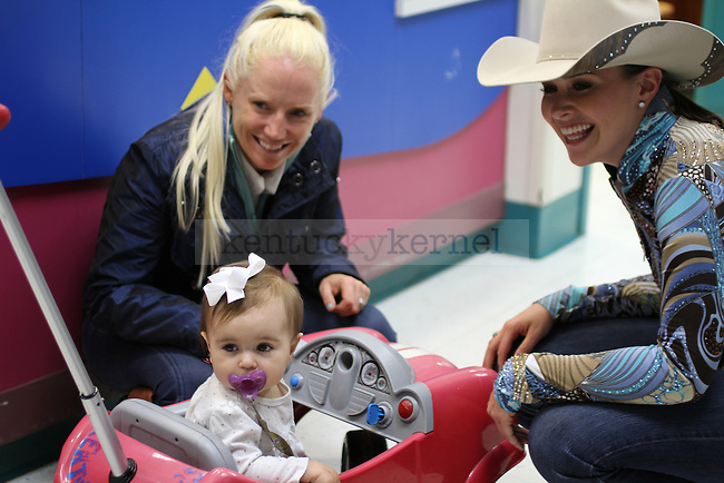 Rolex Riders, Hawley Bennett and Lyndsey Jordan, play with ten month old Keli Moloney from Lexington. The Rolex Riders visited patients and signed autographs at UK Children's Hospital in Lexington Ky., onTuesday  April 23rd, 2013. Photo by: Kirsten Holliday | Staff