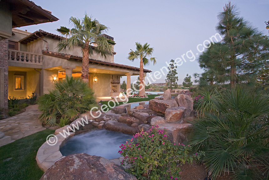 View across swimming pool at luxury home at dusk