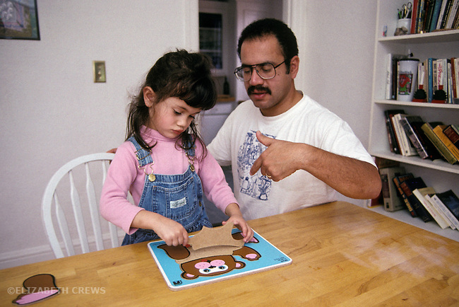 Berkeley, CA Dad, Latino, instructing daughter, three-years-old, on technique for doing puzzle
