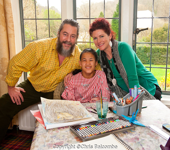 A 15 year-old deaf girl with cerebral palsy, who started life as a baby abandoned on a hospital doorstep, is proving a hit in the world of art.<br /> Paintings by Tjili (pronounced Chilli) Grant Wetherill are selling for thousands of pounds, and two have just been selected by the Royal Watercolour Society for a major London exhibition.<br /> Born in Cambodia, Tjili now lives in Hampshire&rsquo;s New Forest, after being adopted by British couple James and Vik Grant Wetherill, when she was just eight weeks old.<br /> <br /> Pictured: James and Vik Grant Wetherill with adopted daughter Tjili, at their home in the New Forest, Hampshire.<br /> <br /> Pic:  Chris Balcombe<br /> <br /> 07568 098176<br /> Office: 023 80 849187