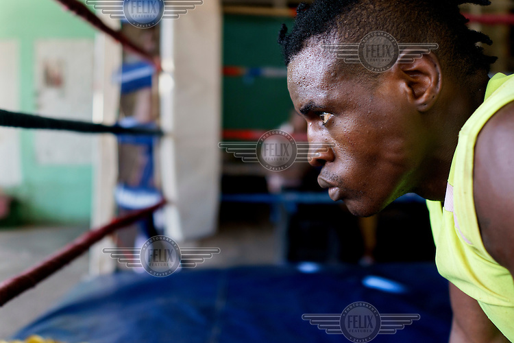 Yomi Shokunbi, a Nigerian living in South Africa, training at George Khosi's Hillbrow Boxing Club. Currently a model and fitness trainer, Yomi hopes to qualify for his boxing license in a few weeks time and become a professional heavyweight boxer.  Hillbrow, in downtown Johannesburg, is the city's most notorious neighbourhood. It is overcrowded, ridden with illegal squats and suffers from high levels of crime much of which is related the thriving illicit drug trade. Against this backdrop, George Khosi's story is not atypical. A childhood spent on the streets, where he survived by committing petty crime and hustling, led to imprisonment at the age of 16. Because he was big and looked older than his age this incarceration was in an adult institution. Here he began to fight since, as he says 'they wanted to make me a woman and I didn't want to be a woman.' When he got out, he took up boxing in earnest. His prospects as a professional boxer looked bright until he was shot and left for dead during a burglary. He lost his right eye and now walks with a limp. His boxing career seemed over but George picked up his gloves again, this time to teach Hillbrow's youngsters. His gym became a place of hope and discipline for local youth, keeping them of the streets and even producing some national champions.