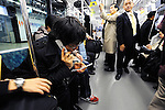 "A man uses two mobile phones on a train in Tokyo, Japan. The Japanese are well known for their civility and politeness,  but a recent governmental campaign to clamp down on lewd behavior that may inconvenience others -- including talking on cell phones and applying makeup while commuting on a train -- was fueled by a decline in everyday etiquette and manners. The series of posters has a headline that reads ""Please do it at home."""