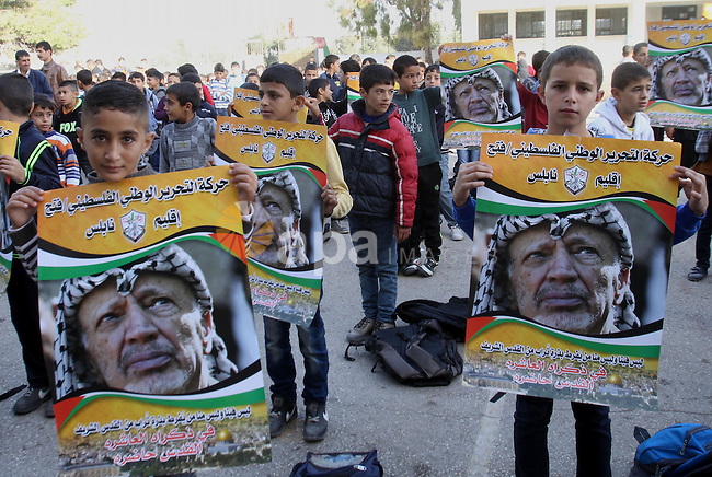Palestinian students hold posters of the late Palestinian leader Yasser Arafat on the ten anniversary of his death, during a rally at A-Najah University in the West Bank city of Nablus, on Nov. 10, 2014. Photo by Nedal Eshtayah