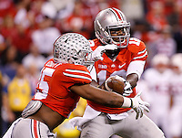 Ohio State Buckeyes quarterback Cardale Jones (12) hands off the ball to Ohio State Buckeyes running back Ezekiel Elliott (15) for a 81-yard touchdown run during the first quarter of the Big Ten Championship game against the Wisconsin Badgers at Lucas Oil Stadium in Indianapolis on Dec. 6, 2014. (Adam Cairns / The Columbus Dispatch)