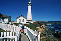 Scenic coastal view of visitors looking out at the Pacific Ocean over a white picket fence at the Pigeon point Lighthouse. San Mateo, California.