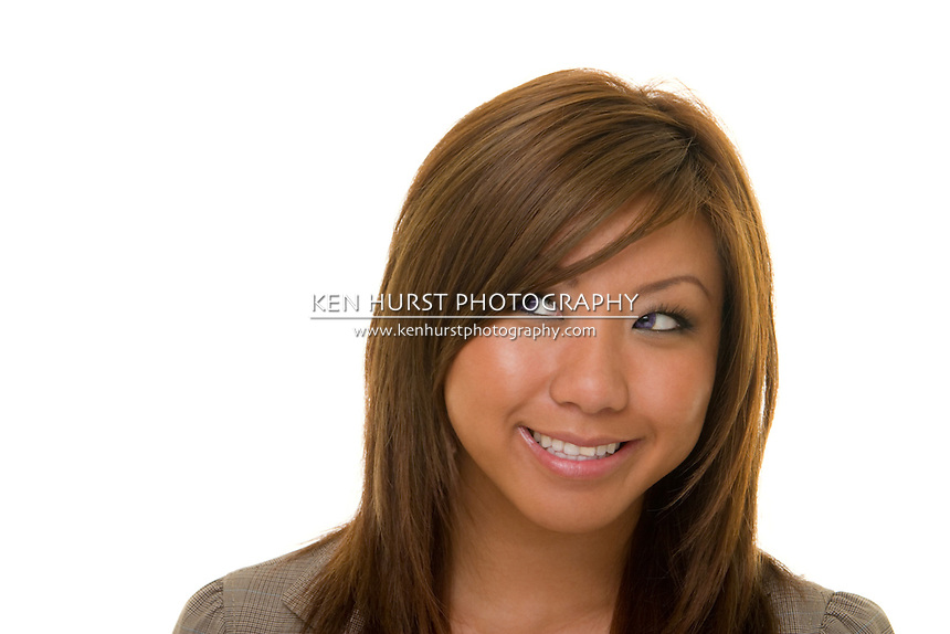 Beautiful young, happy Asian woman smiling and looking to her right.
