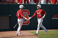 Will Wilson (8) of the North Carolina State Wolfpack celebrates with teammate Evan Edwards (18) after hitting a home run against the Army Black Knights at Doak Field at Dail Park on June 3, 2018 in Raleigh, North Carolina. The Wolfpack defeated the Black Knights 11-1. (Brian Westerholt/Four Seam Images)