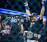 Junior Dos Santos reacts to receiving the World Heavyweight Championship belt from Cain Velasquez after a TKO during Saturday's UFC on Fox.