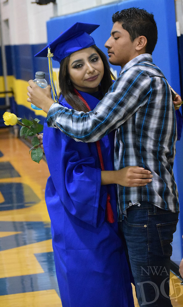 Photo by Mike Eckels<br /> <br /> Cindy Guadarrama (left) gives her brother Marck a rose and a hug just before the receiving of diploma part of the 2016 Decatur High School graduation ceremony in Peterson Gym May 15.