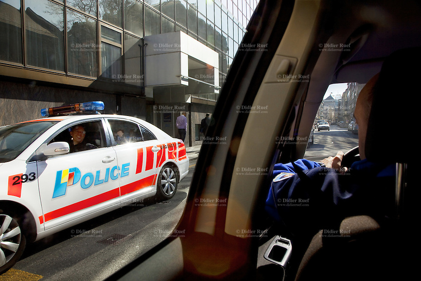 Switzerland. Geneva. Two police officers in two police cars talk to each other in the middle of the Berne street ( rue de Berne). Both policemen are on patrol in the Paquis neighborhood. 27.03.12 © 2012 Didier Ruef..