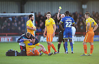 Karleigh Osborne of AFC Wimbledon is shown the yellow card by Referee Philip Gibbs for a foul on Garry Thompson of Wycombe Wanderers during the Sky Bet League 2 match between AFC Wimbledon and Wycombe Wanderers at the Cherry Red Records Stadium, Kingston, England on 21 November 2015. Photo by Alan  Stanford/PRiME.