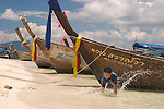 Thai child playing on beach, longboats, Phi Phi Islands, Thailand.