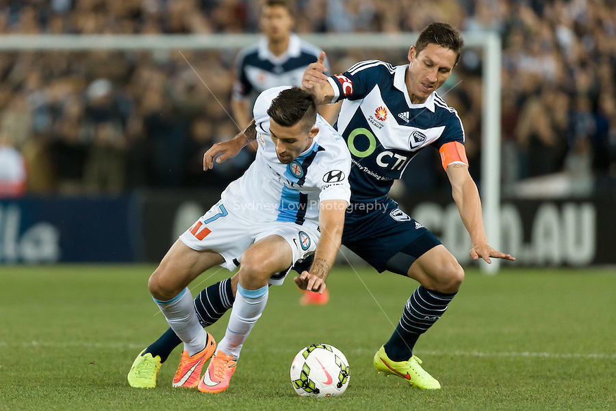 Jason HOFFMAN of Melbourne City and Mark MILLIGAN of the Victory fight for the ball in the round 3 match between Melbourne  Victory and Melbourne City in the Australian Hyundai A-League 2014-15 season at Etihad Stadium, Melbourne, Australia.