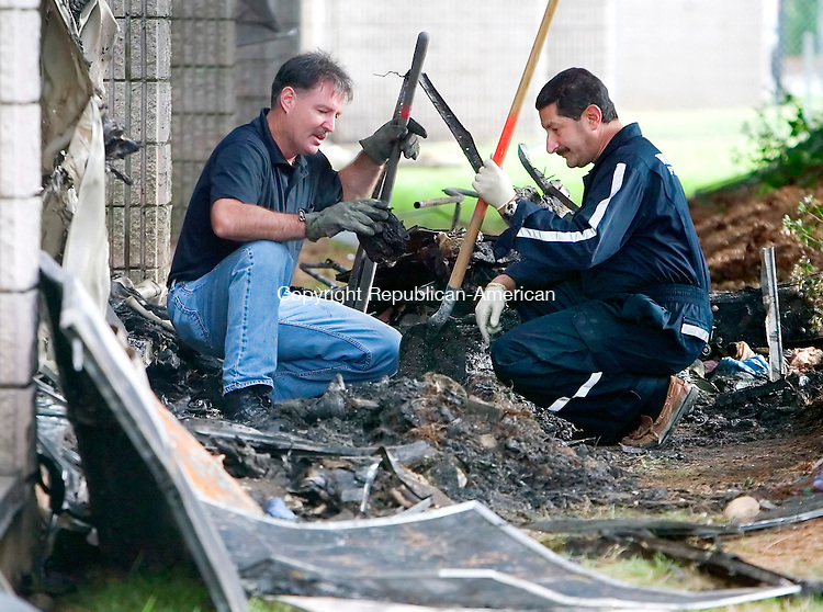 WATERBURY, CT. 11 SEPTEMBER 2008-091108SV02--Fire Investigators Terry Ballou and Dan Aybar dig through the rubble of an apartment fire at 2221 East Main Street in Waterbury Thursday. Steven Valenti Republican-American