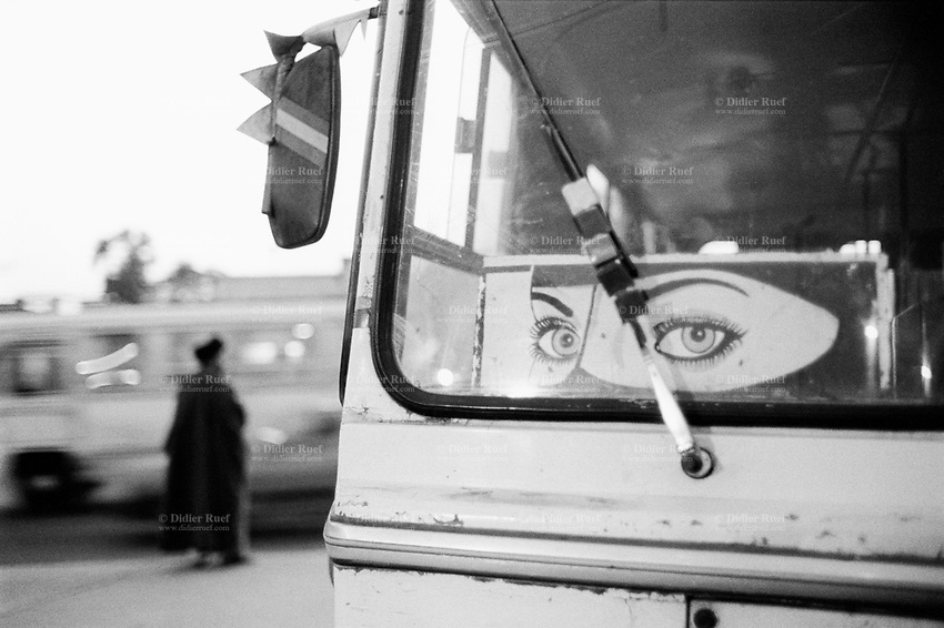 Iraq. Najaf. Sticker on a public bus of a woman's face wearing the niqab. A mullah waits to cross the road on a busy traffic road in the early evening. The mullah is generally used to refer to a Muslim man, educated in Islamic theology and sacred law. The title, given to some Islamic clergy, is the name commonly given to local Islamic clerics or mosque leaders. 26.02.04 © 2004 Didier Ruef .