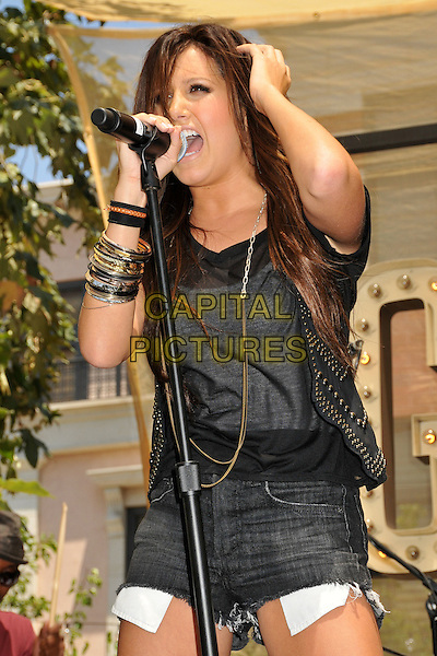 """ASHLEY TISDALE .Ashley Tisdale Promotes her Album """"Guilty Pleasure"""" with a Live Performance at The Grove, Los Angeles, CA, USA..June 27th, 2009.stage concert live gig performance music half length microphone black hand waistcoat grey gray top jean denim cut offs shorts pockets silver gold bracelets singing .CAP/ADM/BP.©Byron Purvis/AdMedia/Capital Pictures."""