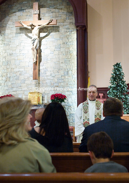 Waterbury, CT- 27 December 2015-122715CM02-  Father Jeremiah Murasso performs a baptism at Blessed Sacrament Church in Waterbury on Sunday.  Father Murasso was recently reinstated after being found not guilty following a sexual misconduct investigation.       Christopher Massa Republican-American