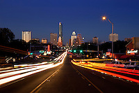 View of downtown South Congress Avenue (Soco) nightlife with Austin Skyline & Texas State Capitol as night car light trails streak past