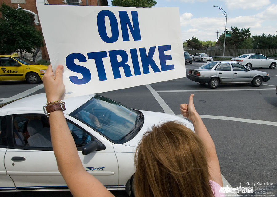 A striking Franklin County Child Support Enforcement Agency worker gives a thumbs up sign to  drivers honking their horns as they pass by a group of strikers outside the service's office in Downtown Columbus, Ohio, Monday, June 12, 2006. About 200 workers are off the job, striking against the county over wages and health insurance.<br />